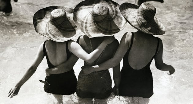 Three women wearing sunhats in pool, rear view (B&W)