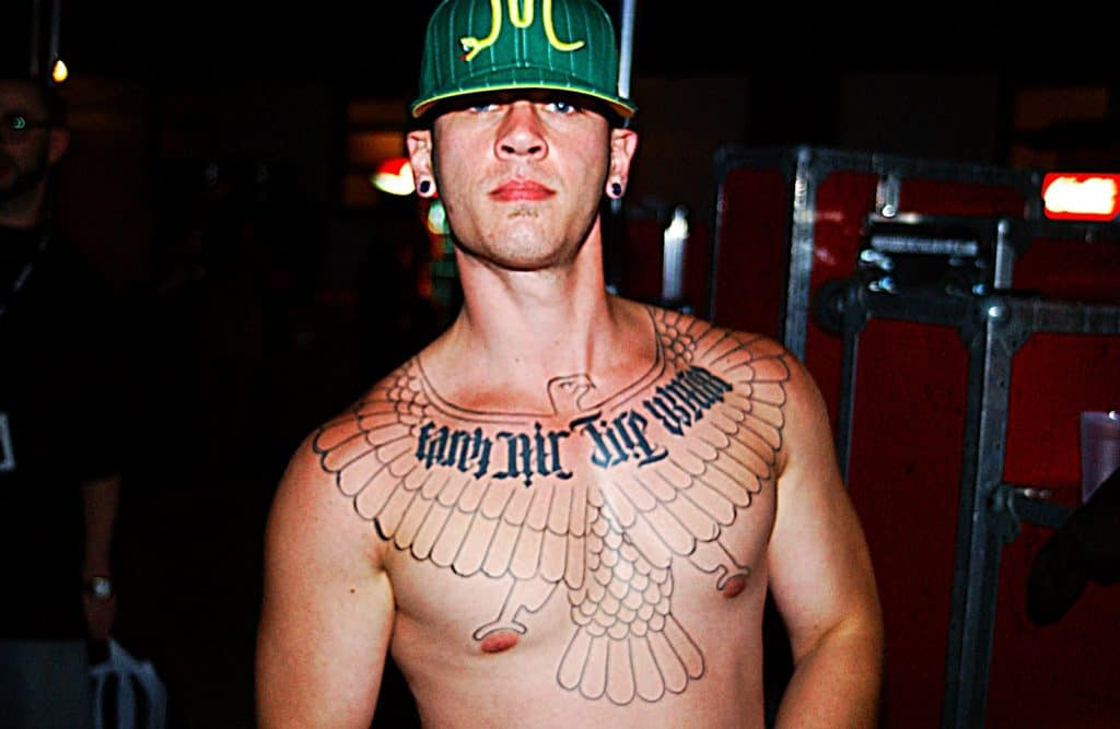 lettering-and-bird-tattoo-on-chest-of-guy
