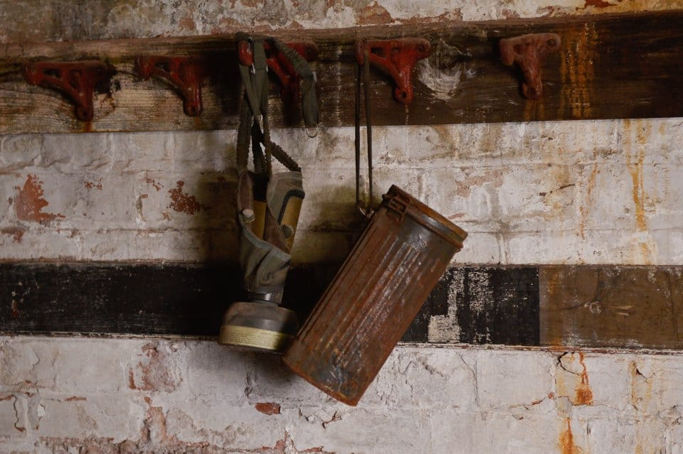 """An old gas mask hanging in the room. These remarkable pictures show a fire station which was left untouched for more than 60 years before it was discovered in the cellar of an old Co Op factory. See NTI story NTIFIRE. The secret fire station is complete with 1920s firefighting equipment, pumps, uniforms and coiled hoses. A half-drunk bottle of lemonade and exercise programmes were also found in the cellar of the former Co Op factory in Dudley, West Mids. Staff at shopfitting company The Allan Nuttall Partnership, which is now based in the building, heard rumours of a hidden fire station but dismissed it as an """"urban myth"""". But when marketing manager Anna Bramford dug out some keys she was astonished to find fire regalia and pumps dating back to the 1920s."""