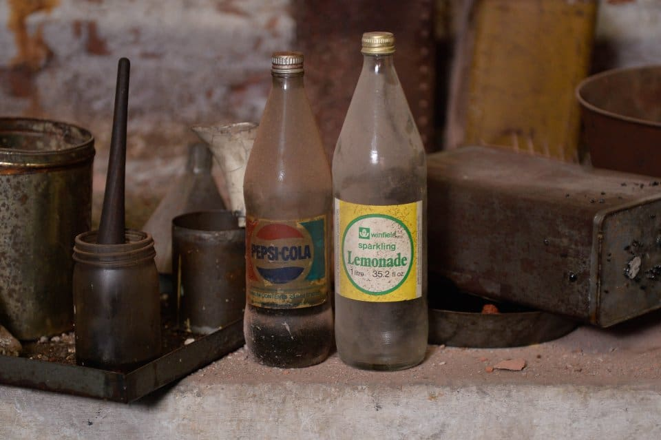 """A half drunk bottle of Pepsi and lemonade just left on the side. These remarkable pictures show a fire station which was left untouched for more than 60 years before it was discovered in the cellar of an old Co Op factory. See NTI story NTIFIRE. The secret fire station is complete with 1920s firefighting equipment, pumps, uniforms and coiled hoses. A half-drunk bottle of lemonade and exercise programmes were also found in the cellar of the former Co Op factory in Dudley, West Mids. Staff at shopfitting company The Allan Nuttall Partnership, which is now based in the building, heard rumours of a hidden fire station but dismissed it as an """"urban myth"""". But when marketing manager Anna Bramford dug out some keys she was astonished to find fire regalia and pumps dating back to the 1920s."""