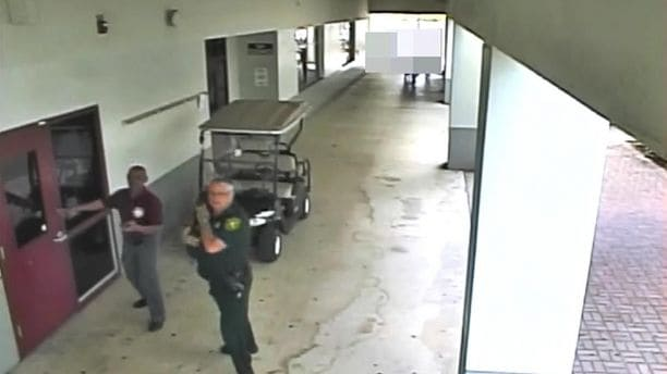 Broward Deputy Scot Peterson stands outside during shooting